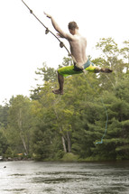 Teenage boy swinging high from rope swing over water and letting go