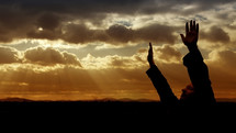 man with hands raised in worship at sunset