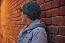 a boy leading against a brick wall