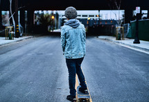a boy skateboarding in the middle of a street