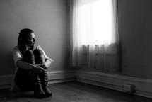 a teen girl sitting in an empty room by a window