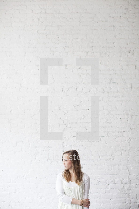 Shy woman standing in front of a brick wall and looking away.