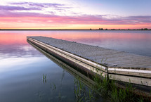 pier over calm water at sunset