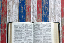 open Bible on weathered red, white, and blue