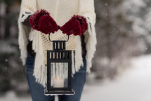a woman holding a lantern in the snow