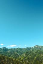 green mountains under a blue sky