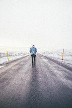 a man standing in the middle of a road alone