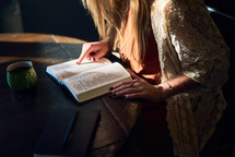 a woman reading a Bible at a coffee shop