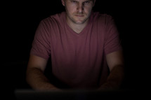 A man illuminated by the light of a computer.