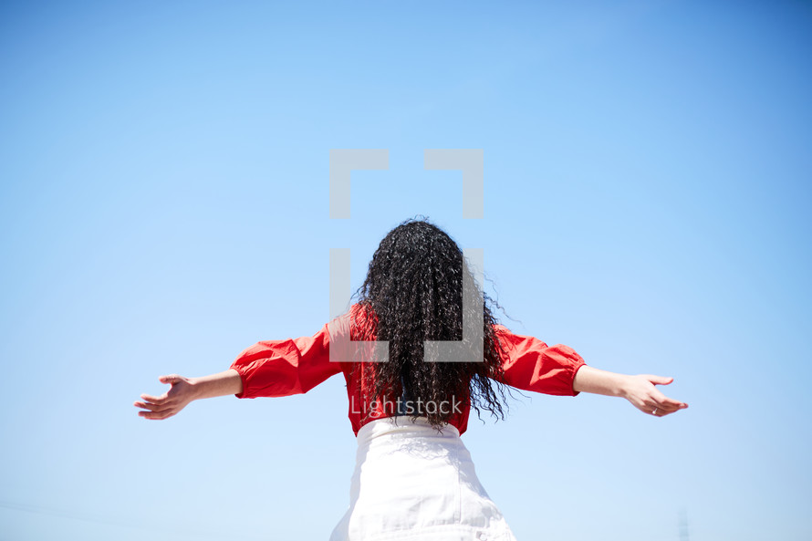 back of a woman with outstretched arms looking up