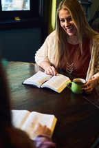 women discussing scripture over coffee