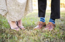 feet of a couple standing in grass