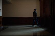 man walking down a hallway