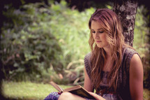 woman sitting under a tree reading a Bible