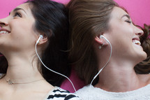 Two young women smiling and listening to music with ear phones.