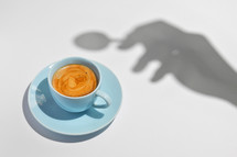 Abstract Cup Of Coffee with a Spoon and Hand Silhouette