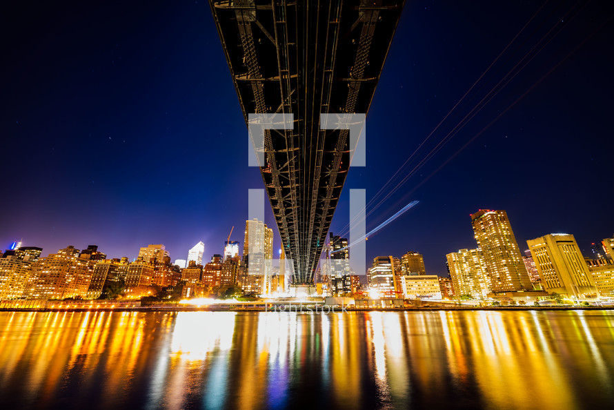 bridge over water and city lights at night