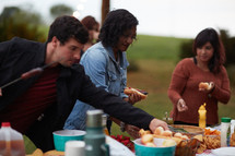 friends gathered around a table getting food at an outdoor party
