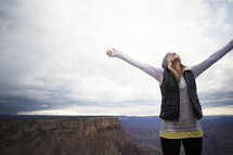 woman standing on a mountain top with raised hands