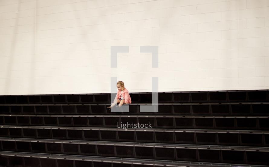 toddler girl sitting on steps outdoors