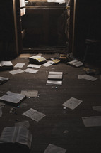 books and pages on the floor of an abandoned house
