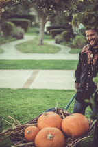 Man moving pumpkins with a wheelbarrow in the yard.