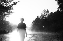 a young man standing by a river under intense sunlight