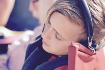 a sleepy child listening to headphones