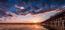 pier at sunset along a beach