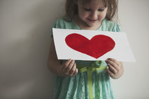 little girl holding a heart painting