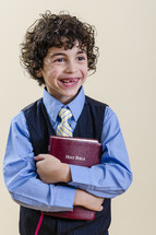 boy child missing teeth smiles as he hold a Bible
