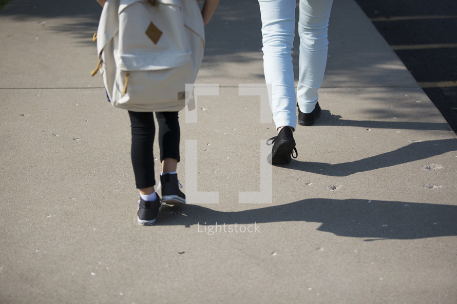 mother and daughter walking to school