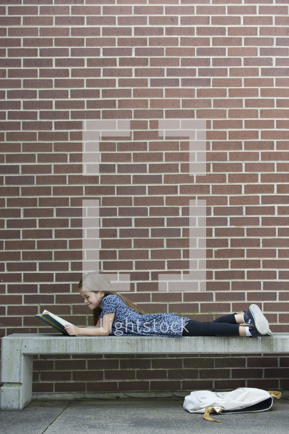 a child on a bench reading a book while waiting for school to start