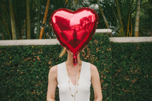 woman holding a heart shaped helium balloon