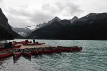 canoes tied to a dock on a mountain lake