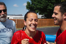 A smiling woman who has just been baptized.