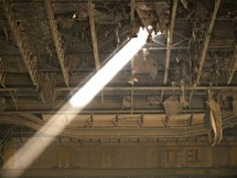ray of light shining through a hole in the roof of an abandoned warehouse