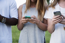 row of young adults on cellphones