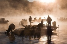 morning fishermen on a boat over steaming water