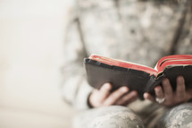 Female soldier reading through an old Bible.