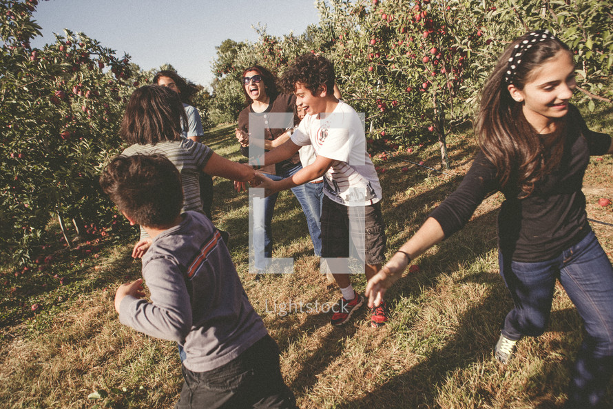 family dancing in an apple orchard