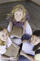 Teen girls sitting on wood floor studying with text books.