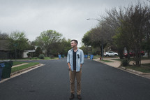 man standing in the middle of a neighborhood street