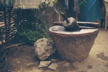 Stone mortar and pestle in the dirt.