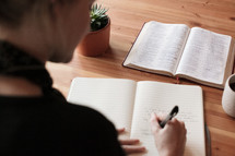 a woman reading a Bible and journaling