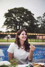 a woman at a dinner party next to a swimming pool