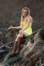 A woman in boots and a yellow dress sitting on a rock outdoors.