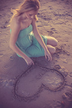 A woman drawing a heart in the sand.