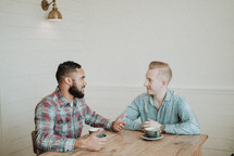 two men talking while sitting at a table drinking coffee