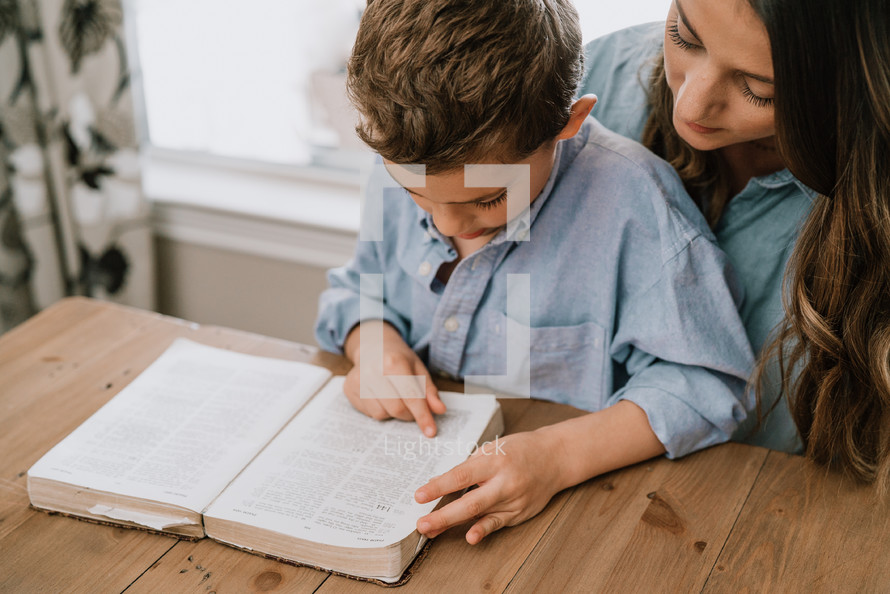 a mother and son reading a Bible together